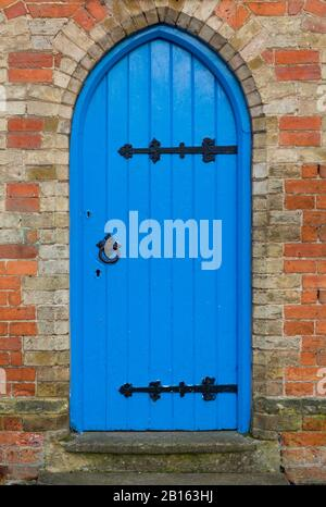 Traditional blue arched door with black ironmongery in a doorway, UK - Stock Photo