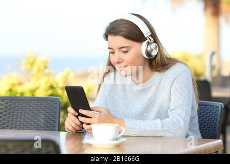 Relaxed girl wearing wireless headphones is listening to music checking smart phone in a coffee shop terrace