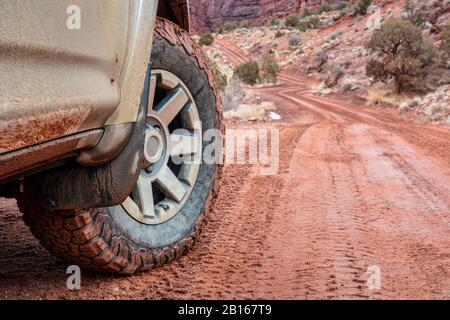 Front wheel of 4x4 SUV car or truck driving on a dirt canyon road - Onion Creek Trail in Moab area, Utah - Stock Photo