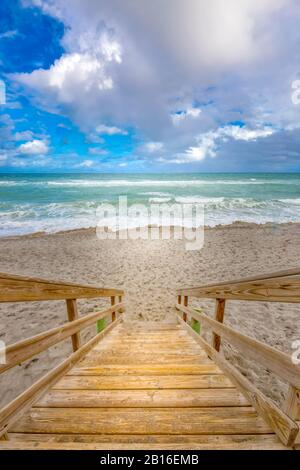 Steps lead down to the beach at Blowing Rocks Preserve in Jupiter, FL. Blowing Rocks Beach features amazing rock formations, and crashing waves. - Stock Photo
