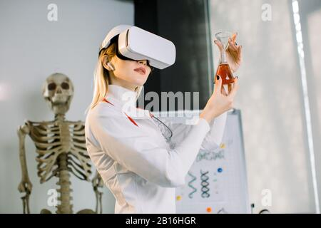 Portrait of young woman scientist, chemist, wearing white coat and virtual reality glasses, studying a new substance in the glass flask. Science, medi - Stock Photo