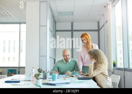 Group of three business people discussing documents while working at table in office, copy space - Stock Photo