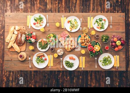 Large festive table with a huge amount of delicious and healthy food. Festive table set for six people. Wooden background top view mock-up. Wooden bac - Stock Photo