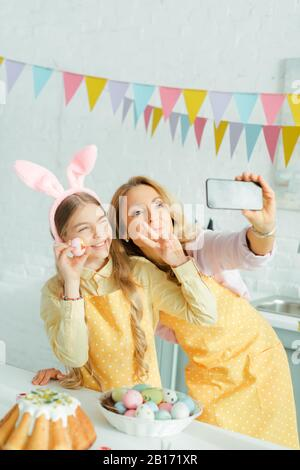 selective focus of happy mother and daughter in bunny ears showing peace sign while taking selfie with painted easter egg - Stock Photo