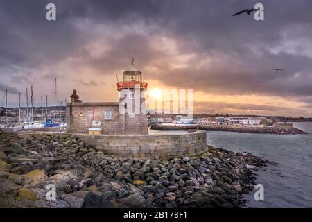Howth Lighthouse with flying seagulls at beautiful sunset. Yachts and sailboats in harbour, Dublin, Ireland - Stock Photo