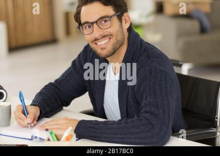 young disabled man studying at home - Stock Photo