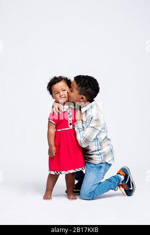 Boy kissing his little sister - Stock Photo