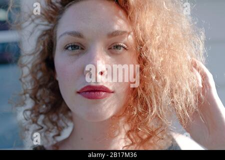 Portrait of red-haired woman looking at camera, hand in hair - Stock Photo