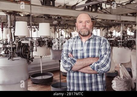 Portrait of a confident mature man in a textile factory - Stock Photo