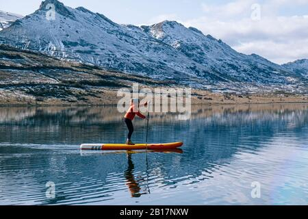 Woman stand up paddle surfing on a lake