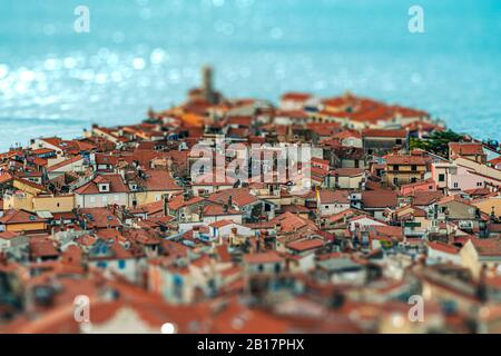 Tilt-shift effect of beautiful slovenian seaside town Piran with narrow lanes and streets and old roofs top view from above