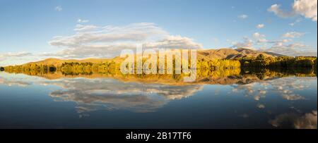 New Zealand, Franklin District, Glenbrook, Forested hills reflecting in Wairepo Arm lake in autumn
