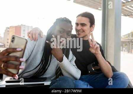 Happy young couple taking a selfie at tram stop