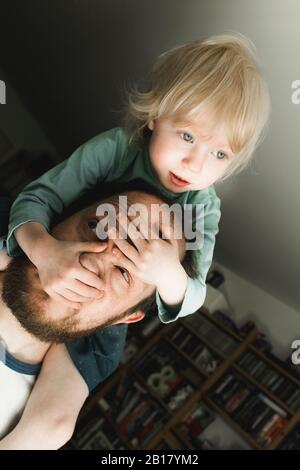 Father carrying little daughter on his shoulders at home - Stock Photo