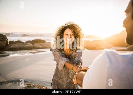 Happy couple holding hands on the beach at sunset