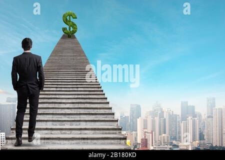 Back view of young businessman climbing stairs with dollar sign on city sky background. Finance, Rich, Success and employment concept. - Stock Photo