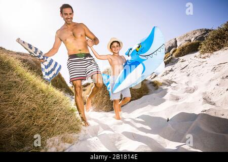 Father and son with inflatable shark walking through the dunes to the beach - Stock Photo