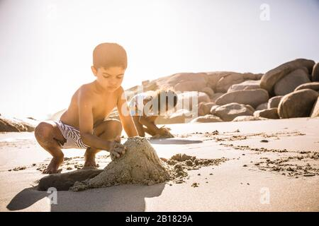 Boy buliding sand castle on the beach together - Stock Photo