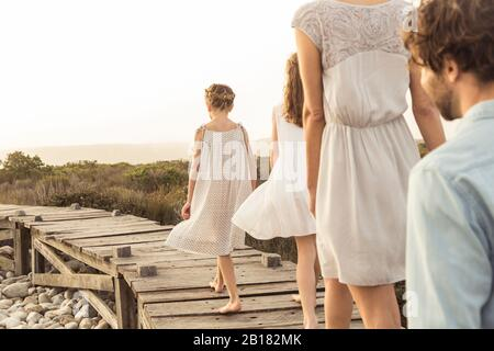 Large family enjoying the sunset on a boardwalk - Stock Photo