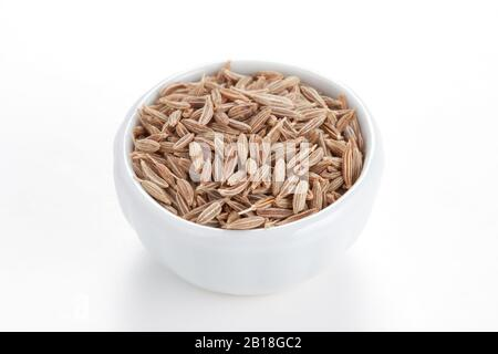 Cumin seeds in a white bowl on white background. Second most popular spice in the world after black pepper.