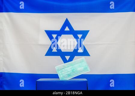 Israeli Elections. Medical face mask in a box for ballot in election on Israel flag background.. Israelis quarantined for coronavirus will get voting booths for March election. - Stock Photo