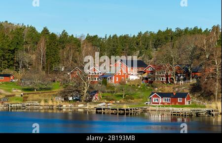 Picturesque summer houses painted in traditional falun red on dwellings island of the Stockholm archipelago in the Baltic Sea in the early morning. - Stock Photo