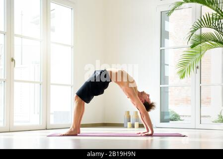 Shirtless young man practicing yoga doing bridge pose, exercising indoors in bright spacious room with high windows. Low angle side view - Stock Photo