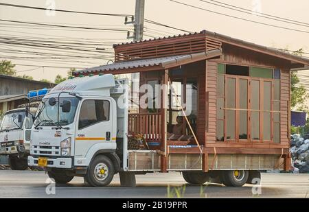 A small wooden house being transported on a truck. - Stock Photo