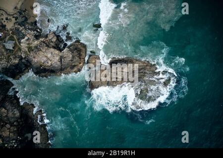 Aerial View to azure ocean waves breaks on the rocks. Kerala, India. - Stock Photo