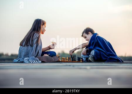 Two young cute little friends, boy and girl having fun while playing chess sitting by the lake in the evening. Kids are playing. Friendship. - Stock Photo