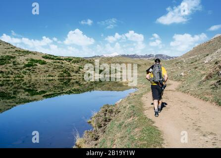 A man makes trekking walking along a road with a lake next to it and mountains in the background on a sunny day - Stock Photo