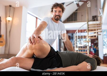 A professional masseur-therapist doing medical massage of legs. A middle-aged strong man receiving therapeutic massage in the medical center