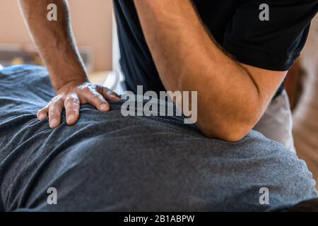 A professional masseur doing back massage. Therapeutic body massage treatment. Osteopathy and sports injury rehabilitation concepts