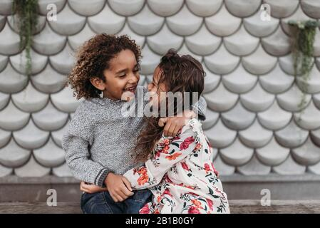 Cute siblings smiling and laughing at each other while hugging outside - Stock Photo