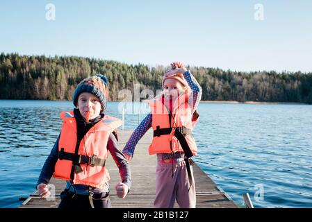 brother and sister playing at the beach wearing life jackets in winter - Stock Photo