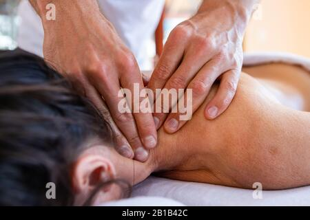Young woman in the spa receiving neck massage. Focus is on human hands. Female patient receiving massage on neck and shoulder