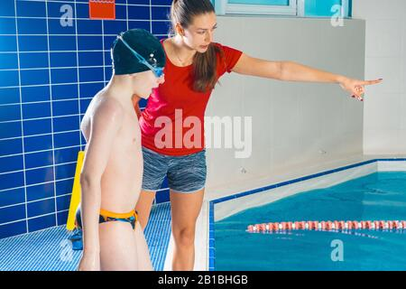 Female Coach In Water Giving preteen boy swimming Lesson In Indoor Pool
