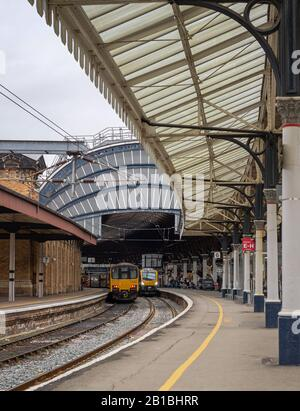 Typical view of a railway station platform with two trains waiting to depart.  An ornate, curved metal and glass 19th Century canopy is above. - Stock Photo
