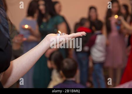 Holding hands on henna candle . She holds the candle in his hand Henna party . - Stock Photo