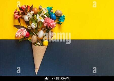A bouquet of bright spring flowers and colorful easter eggs. View from above. Top view. Happy Easter, springtime concepts. Put your text in copy space - Stock Photo