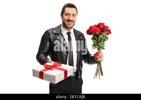 Man in a leather jacket holding a gift box and a bunch of red roses isolated on white background - Stock Photo
