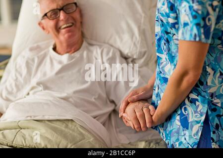 Smiling senior man being comforted by a female nurse while lying in bed. - Stock Photo