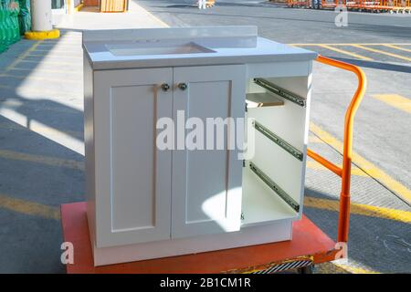 A white cabinet with the drawers removed sits on a trolley cart outside a home improvement store. - Stock Photo