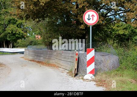 Give way to oncoming vehicles round road sign mounted on top of metal pipe with striped red and white warning sign in front of thick temporary flood - Stock Photo
