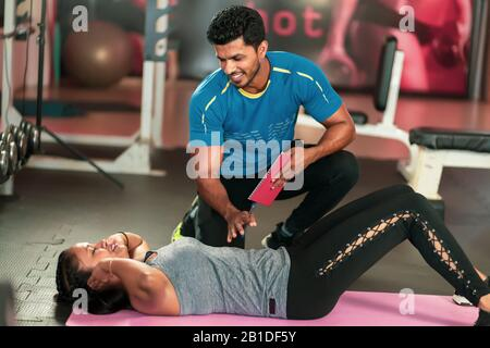 Trainer helping young woman to do abdominal exercises on the background of fitness balls. Beautiful woman doing abs on a mat and a man helps her in - Stock Photo