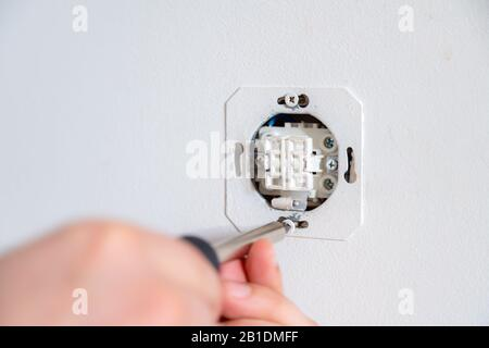 Electrician fixing electric socket with a screwdriver. Handyman working on switches and sockets indoor - Stock Photo