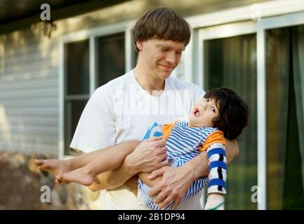 Caucasian father holding disabled biracial son in arms outside of home - Stock Photo