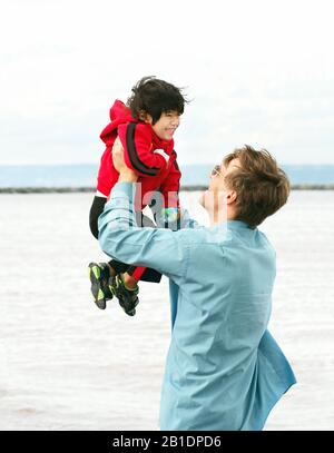 Caucasian father lifting up disabled little boy in his arms overhead outdoors by lake - Stock Photo