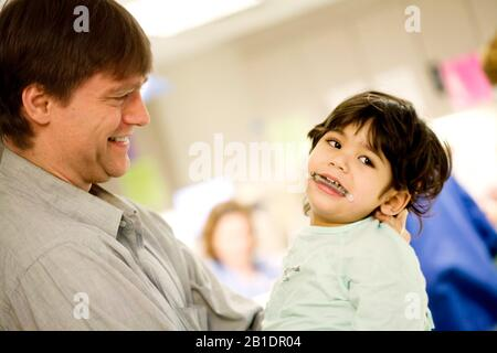 Caucasian father holding sick disabled little boy in surgical gown in hospital before surgery. Child has medical mouth device in place. - Stock Photo