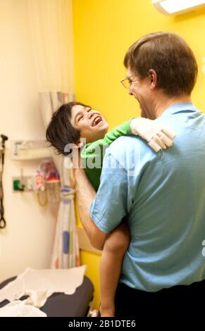 Caucasian father holding sick biracial disabled little boy in doctor's clinic room while waiting for doctor at hospital, smiling - Stock Photo
